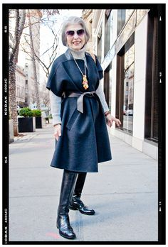 """""""When I first saw this woman, 'chic and luxurious' came to mind. The short-sleeve cape is an exquisite outwear piece and layers beautifully over the chunky turtleneck. The black riding boots polish off the look and the necklace is an artistic statement. This lady has great style and is an influence for all ages."""" Stylish Older Women, Mature Fashion, Modest Fashion, Grey White Hair, Fashion Over Fifty, Outfits Mujer, Black Riding Boots, Wrap Coat, Advanced Style"""