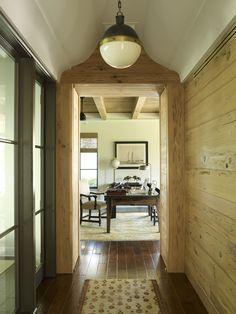 conference room hallway with #iron windows, pecky cypress walls, #visualcomfort lighting, custom desk Kate Jackson Design and Pursley Dixon Architecture