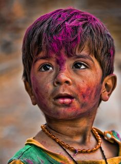 Engrossed look of a colorful, innocent kid watching festival of colors.    Event: Holi 2011, Mumbai.