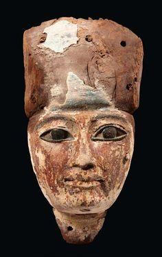 Masque de sarcophage représentant le visage d'un homme à la carnation rouge, coiffé de la lourde perruque; il était paré de la barbe postiche. Les yeux, aujourd'hui refaits, étaient incrustés. Bois et traces de polychromie. Égypte, Troisième Période Intermédiaire.