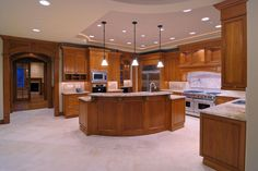 A wood and light tile kitchen with archways leading out into various other parts of the home. The tray ceiling is lit by both tube lighting around the rim and by recessed lighting dotting the ceiling. A curved island with an additional sink takes up real estate in the center of the gaping kitchen.