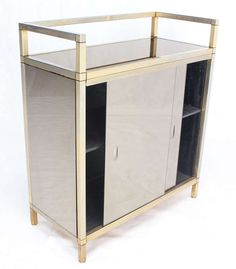 Mid Century Smoked Glass Server Cabinet w/ Sliding Doors   From a unique collection of antique and modern cabinets at https://www.1stdibs.com/furniture/storage-case-pieces/cabinets/