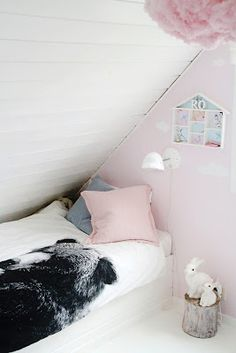 Light pink cloud walls are a must. Love the pink and grey pillows, along with those fuzzy pom poms.