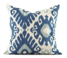 Beautiful modern ikat pillow cover in different shades of blue on an oatmeal background. The pillow cover features a soft medium weight 100% cotton