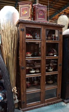 The Alamo Hutch is a large, rustic bookcase, or hutch, made from solid mesquite wood, featuring paneled glass windows on three of its sides.