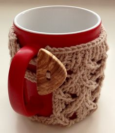 Knitted lacy mug cozy with handmade wooden button