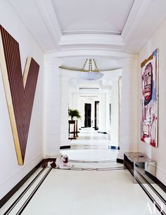 Bold artworks stand out against the white walls of this elegant hallway at an art collector's home. | archdigest.com