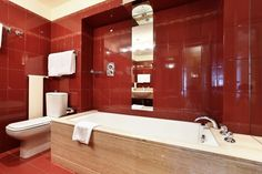 A bathroom featuring a large soaking tub and bold red tile. Do you like the tile border?