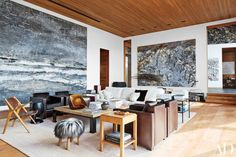 Anselm Kiefer paintings preside over architect Peter Marino's Rocky Mountain living room, where a quartet of Marino-designed Poltrona Frau armchairs in leather and pony skin is joined by a stool covered in Icelandic sheep fur; the gilded-copper tabletop sculpture is by Hervé Wahlen, the carpet was custom made, and the floor planks are reclaimed teak.
