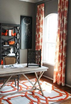 Chic orange office design with gray wall spaint color, white tufted slipper chair, black accent table, white & orange, curtains, rustic sawhorse desk and Coral Arabesque Rug.