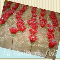 Clavel rojo, jaspeado en blanco los bordes,  con receptáculo verde y lazo.  La casita de Puli