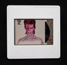"""David Bowie, a music legend, features on a set of Royal Mail special stamps issued in 2017.  This 1st class stamp design shows the 1973 'Aladdin Sane' album cover.   The unused stamp is encased in a vintage slide mount, with glass, making this a unique piece of jewellery. Yuzen paper is used to highlight the vinyl breakout detail. It is square in format and dimensions are approximately 2"""" x 2"""" - 50mm x 50mm.  A nickel plated brooch pin with safety catch is used as a fastening."""