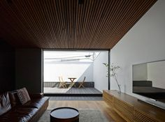 The living room also opens onto a private terrace, concealed within the entrance's cantilevered form. It serves as a secluded space to take in the sun. Thanks to the sizeable opening between the living room and terrace, it brings yet more light into the home. The terrace's table and chairs are from Ikea.