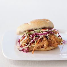 Pulled chicken tossed in a light North Carolina barbecue sauce is piled into soft buns and smothered with creamy coleslaw for these excellent sandwiches.