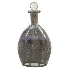 "Glass decanter with an antiqued smokey finish and multifaceted stopper.     Product: DecanterConstruction Material: GlassColor: Antique smoke etchedDimensions: 11"" H x 6"" W x 1"" DCleaning and Care: Wipe clean"