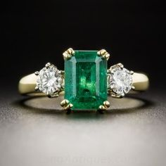 A 1.51 carat, bright vibrant rich green emerald-cut emerald, radiates between a matched pair of sparkling white round brilliant-cut diamonds, totaling .38 carats, in this traditional classic late-20th century vintage three-stone ring. Crafted in 18K yellow gold. Currently ring size 5 3/4.