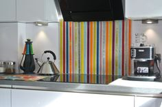 When you look at the image above, what do you see at first? Is it the splash of color that the splashback adds to the kitchen, or is it the way in which all the decoration matches? From the handles of the cutlery, the glass splashback and the surface of the countertop, this kitchen is just perfect for this splashback. It features multiple colours that run vertically down the fused glass, but they manage to tie in with the otherwise neutral decor of the kitchen.