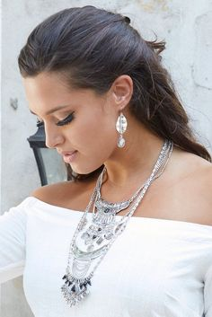 Amp up your attire with the show-stopping Silver Layered Tribal Necklace! This intricate statement necklace adorns your neckline with different chains, patterns, beads, and shiny black gems. Pair with the matching silver drop leaf earrings.