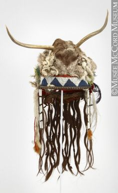 Headdress, Assiniboine or Nakoda. 1850-1900, 19th century. Felt cap, cotton cloth, hide, deer antlers and cranial fur, ermine fur, human? hair, glass beads, brass tacks, stroud, feathers, brass beads, porcelain? beads, canvas cloth, metal beads, wool yarn, resin (glue), cotton string, sinew. 33 x 69 cm. Gift of Miss Mabel Molson. M5349 © McCord Museum