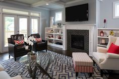 Windows, French doors, white trim and white built-ins help create a bright, airy atmosphere in this comfortable living room. Throw pillows and decorative accents lend cheerful color to the chic design.