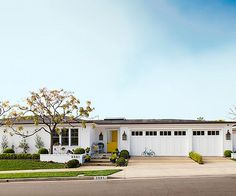 A colorful yellow door draws attention to the welcoming entry of this mid-century ranch house. #bhg