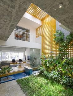 Double height living spaces around the central indoor courtyard garden and pond with light filtered through perforated steel plates and glass, Hyderabad, Telangana, India