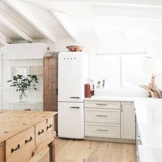 Light and casual kitchen with smeg fridge and light wood floors