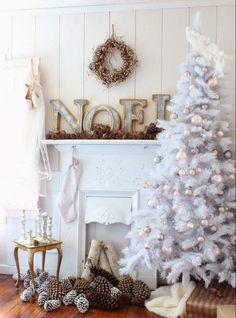 sapin de Noël blanc décoré de boules de Noël en argent et rose pâle placé à côté de la cheminée blanche