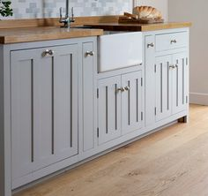 Soft Grey kitchen cupboards with butcher block counters.