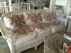Antique white wicker couch with rose pattern cushions