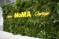 At MoMA's Party in the Garden in April, the arrivals backdrop—featuring the Cartier and MoMA logos rendered in neon and marquee lights—echoed the dense arrangements of tropical greenery found inside the dinner space.