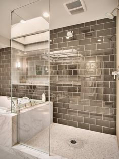These shiny grey subway tiles, in the bathroom below, sparkle from the light and…