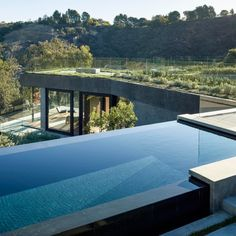 Walker Workshop's Californian house for a concert violinist features an infinity pool that stretches along the edge of outdoor terraces beneath the boughs of one of the site's protected oak trees