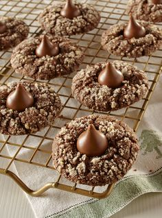 Caramel filled chocolate candy kisses top a gooey chocolate and pecan cookie. A new version of the Peanut Butter Blossom will be a great addition to your Christmas cookie platter.