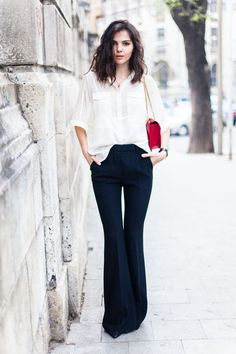 Navy flares with a white blouse + red bag.