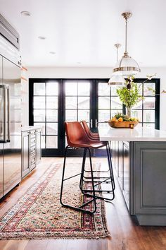 Modern kitchen with industrial pendant lights, leather barstools, and a Persian area rug