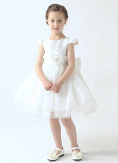 White organza short flower girl dress. Cap sleeve satin bodice is accented with beautiful embroidered detail and 3D flowers at waist. Knee length puffy skirt with draped detail and ruffle trim for a look that is girly and fun. Bow accent on zip back.