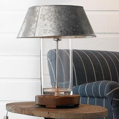 "Rustic Modern Galvanized Table Lamp Modern and rustic elements come together to create this casual eclectic clear glass table lamp. Each wood base is fashioned from 19th Century timber salvaged from old buildings throughout Europe and hand-finished in a natural beeswax. The galvanized shade and chrome accents add to the modern lodge style. Glass cylinder base can be filled with rocks, pebbles, sand or whatever fits your space and mood. 60 watt medium base lamp max. (19""Hx15""W) Supplied with… Modern Lodge, Rustic Modern, Clear Glass Table Lamp, Lodge Style, Old Buildings, Lamp Bases, Chrome, Lights, Wood"