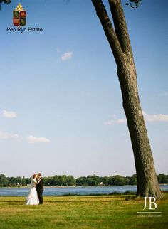 A bride and groom on the front lawn of the Pen Ryn Estate. A beautiful backdrop of the Delaware River. Located in Bucks County PA. 215.633.0600 Photography: Jordon Brian Photography