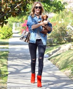 Supermodel chic: The Burberry model teamed ripped black jeans and a pair of bright red ank...