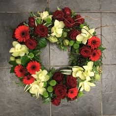 A stunning, modern funeral wreath featuring grouped red and green flowers including roses, gerbera and orchids with textured foliage and a twisted willow twig accent. Flower Wreath Funeral, Funeral Bouquet, Funeral Flowers, Wedding Flowers, Funeral Floral Arrangements, Flower Arrangements, Fresh Wreath, Funeral Sprays, Funeral Tributes