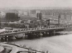 1954   Opening Utrechtsebrug over de Amstel. De Utrechtsebrug verving uiteindelijk de 'gaspont' die tussen de Amsteldijk en de Korte Ouderkerkerdijk voer. De naam van de brug is bepaald door een prijsvraag uitgeschreven door de krant Het Parool. Op de foto ook textielbedrijf ATEK (nu Ford Nederland) en De Mirandabad te zien.