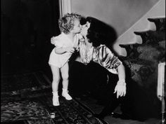 """clarabowarchive:  Motherly Love ♥ Clara Bow kisses her firstborn son, Rex """"Tony"""" Bell, Jr. ♥ Although it's hard to see, there's also a dog sitting by Clara! ☆ Screencap from  Clara Bow: Discovering the """"It"""" Girl ☆"""