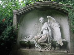 Stone Angel seated on coffin looking away Wood-lawn Cemetery NYC Statue New York City wings woodlawn tomb marker sculpture tombstone graveyard grave yard serenity lady turning grief grieving mourning mourner mourn