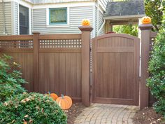 """V3215SQ-6 6' Tongue & Groove Vinyl Privacy fence with Square Lattice top and Majestic™ 8"""" x 8"""" end posts in Grand Illusions Vinyl Woodbond Walnut Grain (W103). Also shown is VBG2 Solid T Crowned Walk Gate."""