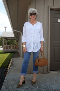Great look with simple jeans and a white blouse and also nice grey hair and great sun glasses.
