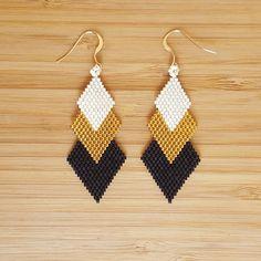 Boucles en perles de verre Miyuki entièrement cousues main. Perles de couleur noir mat et dorées à lOr fin 24 carats. Attaches dorées à lOr fin 14 carats.    Longueur : 7cm