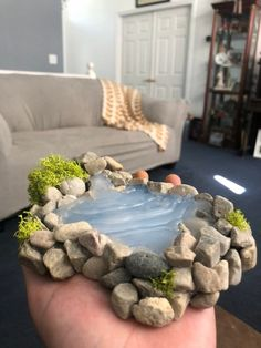 This is a miniature pond with a waterfall attached. The base is made with clay while the surroundings are made with rocks and moss and the water is designed with hot glue. Fairy Garden Furniture, Fairy Garden Houses, Fairies Garden, Garden Pond, Miniature Crafts, Miniature Fairy Gardens, Barbie Furniture, Furniture Legs, Furniture Design