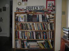 "David Fulmer's bookshelves: ""Past, Present, Future - Queen Street is where I grew up. Yes, those are Rocky & Bullwinkle dolls, too. My favorite books - and room for more of my own at the top. It's a mess and I like it that way."""
