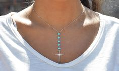 This necklace catches the eye with a lengthy pendant that highlights five bright turquoise stones leading down to a sterling silver cross